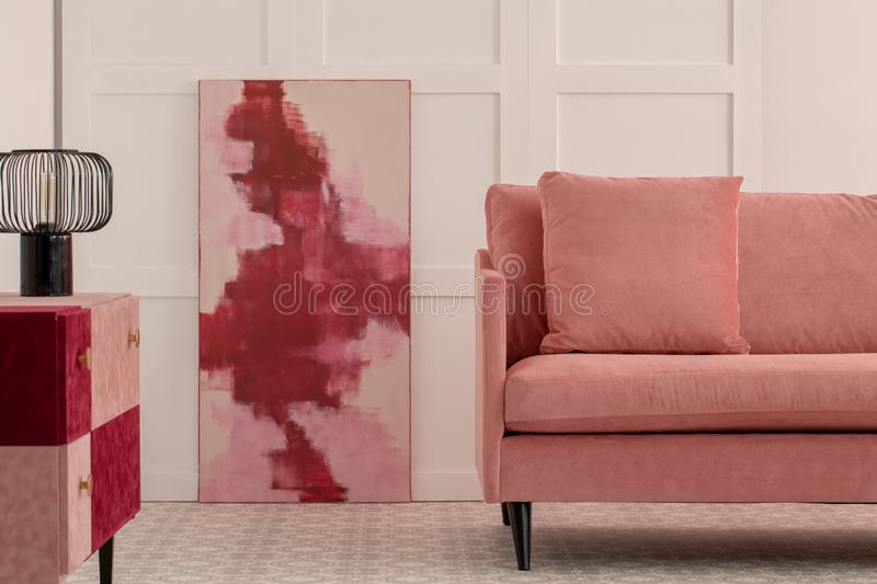 Burgundy and pastel pink abstract painting in white living room interior with velvet sofa stock photos