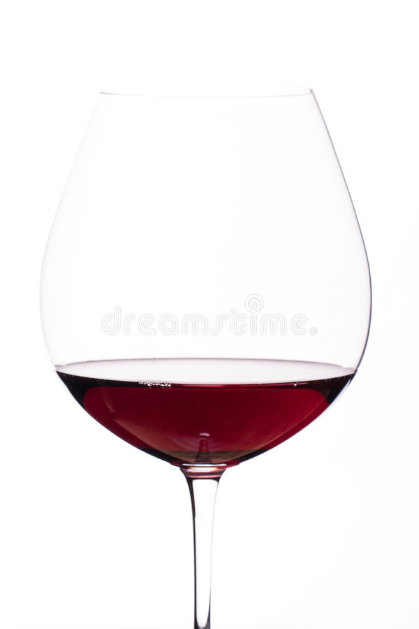 Burgundy red wine in a glass. In front of a white background royalty free stock image