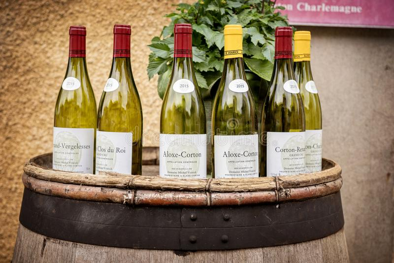 Burgundy wine bottles over a barrel. BURGUNDY, FRANCE - Burgundy wine bottles over a barrel. Burgundy region of France famous for its excellent wines royalty free stock photos