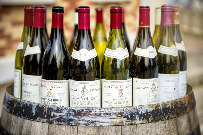 Burgundy wine bottles over a barrel royalty free stock photography