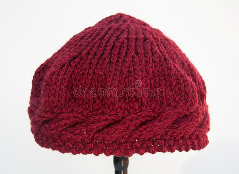 Burgundy wine color knit hat isolated. On light background.  This fiber art is wool yarn in deep maroon color with cable stitches around the brim area of this royalty free stock photo