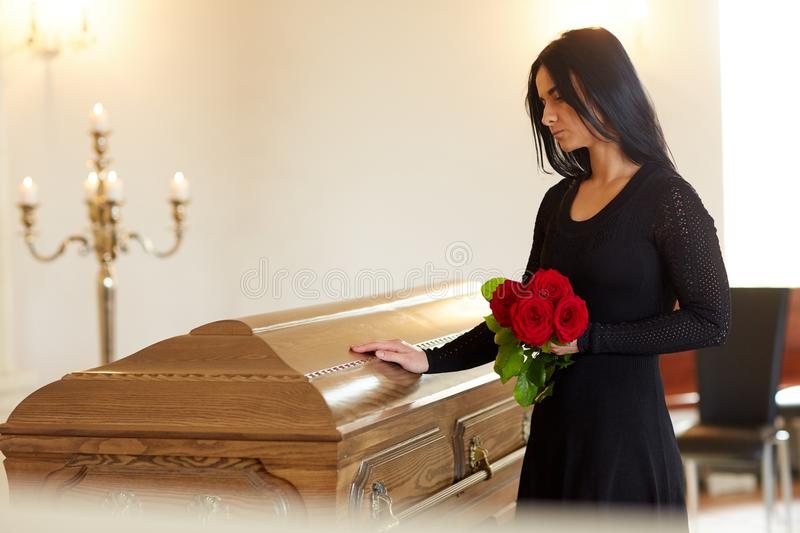 Sad woman with red rose and coffin at funeral stock photos