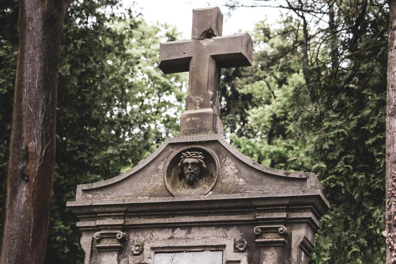 Burial vault in the cemetery, a large stone cross, the image of Jesus on the burial vault stock images