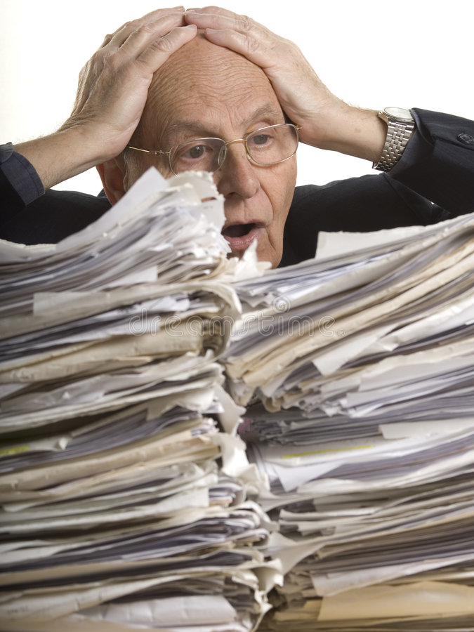 Buried in papers. Business man with the table full of dossiers royalty free stock image