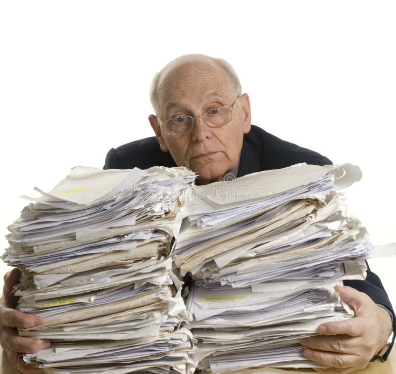 Buried in papers. Business man with the table full of dossiers stock photos