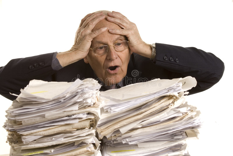 Buried in papers. Business man with the table full of dossiers stock photography