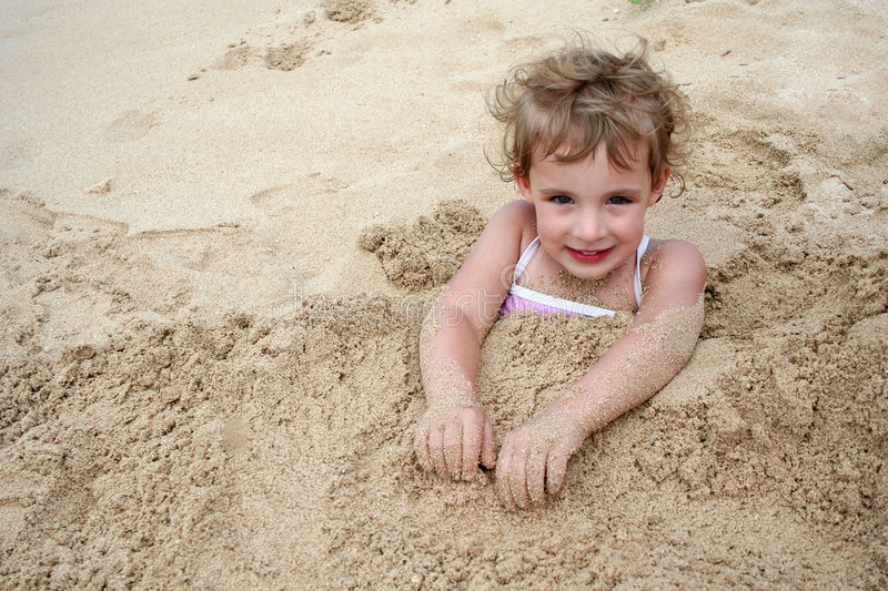Buried in the Sand. A little girl smiles at the camera after being buried in the sand stock photo