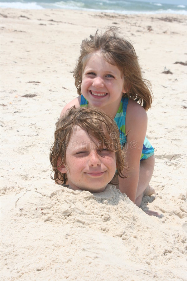 Buried in the sand. Kids playing and being buried in the sand royalty free stock image