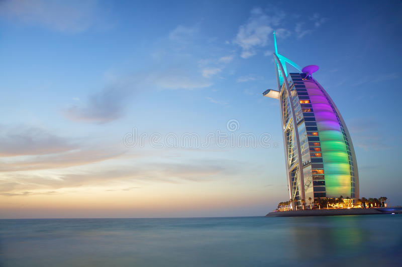 Burj Al Arab. Scenic view of Burj Al Arab colorful illuminated in different colours with cloudscape background, Dubai, United Arab Emirates royalty free stock photos