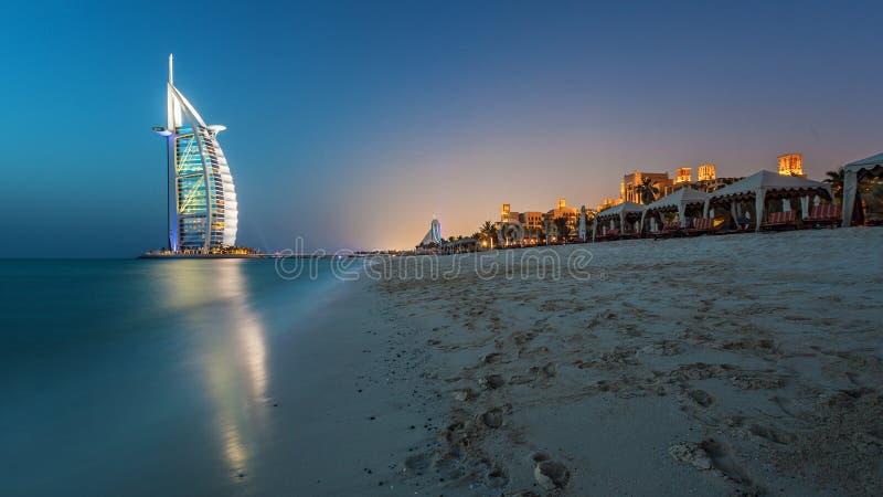 Burj Al Arab på solnedgången med lyxig strandsikt fotografering för bildbyråer
