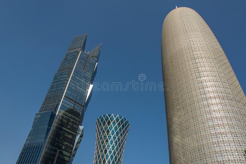 Burj Doha (Burj Qatar, torre de Doha), la torre de QIPCO y la torre de la palma contra el cielo azul claro, se cierran encima de  foto de archivo