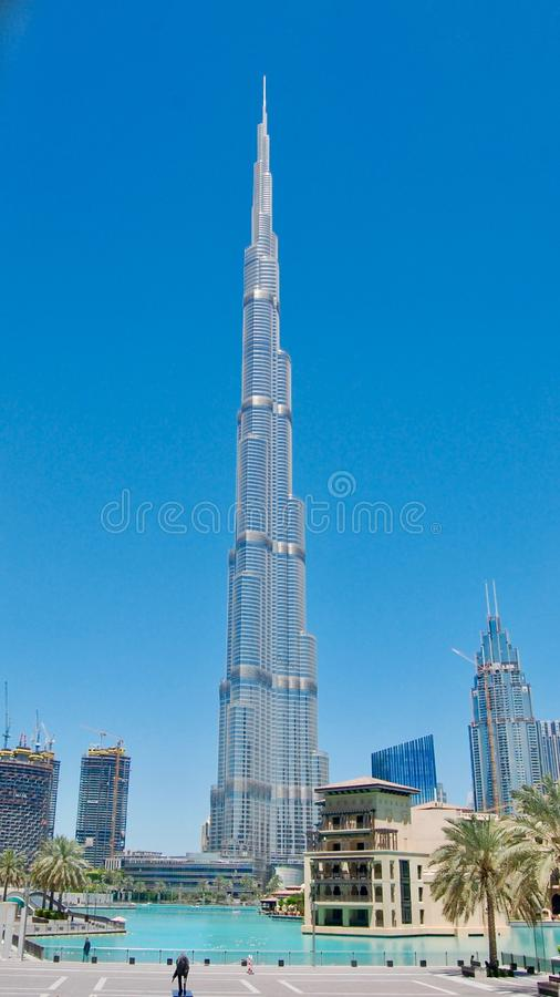Burj Khalifa world`s tallest tower against a deep blue sky background in Dubai, United Arab Emirates with reflective pond in front royalty free stock photography
