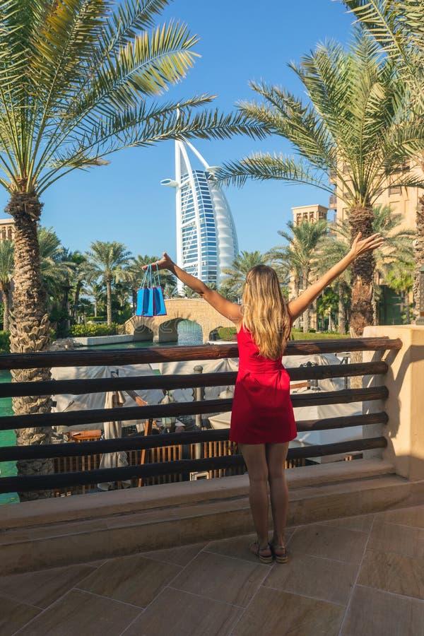 Burjal Arabier van Madinat Jumeirah door jonge toeristenvrouw wordt gezien kleedde zich in rode kleding die stock fotografie
