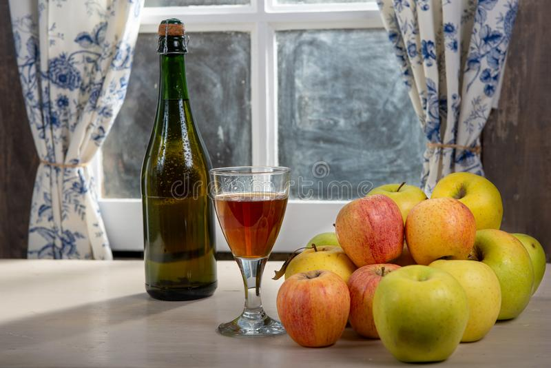 Burk och glas av cider med äpplen nära fönstret, i det rustiska huset arkivbilder