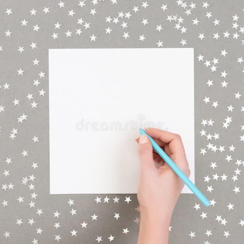 Burla navideña con estrellas de confetti plateadas de fondo gris La mano de una mujer escribe una lista Feliz Año Nuevo fotos de archivo libres de regalías