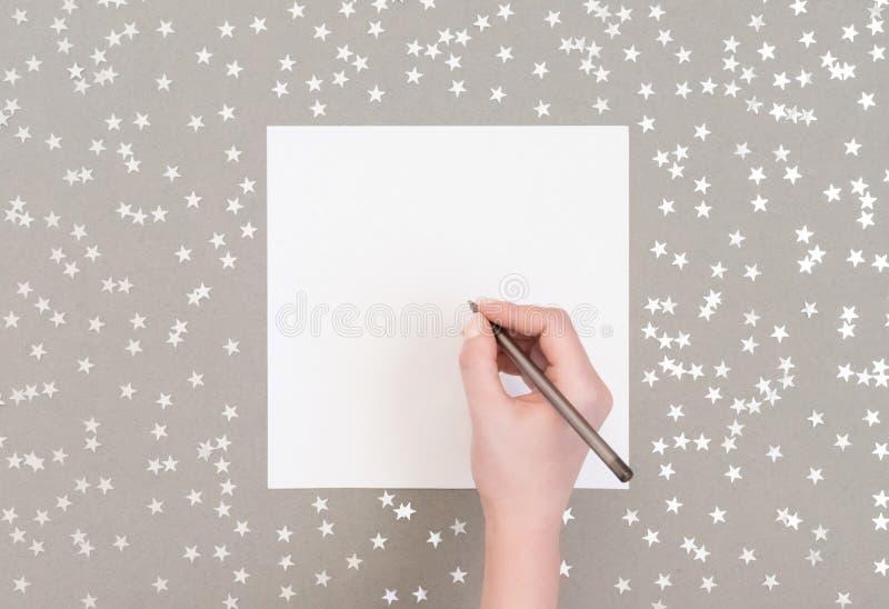Burla navideña con estrellas de confetti plateadas de fondo gris La mano de una mujer escribe una lista Feliz Año Nuevo foto de archivo libre de regalías