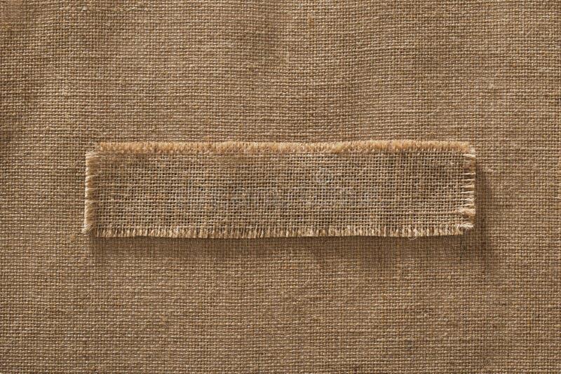 Burlap ετικέτα κομματιού πλαισίων υφάσματος πέρα από Hessian λινού υφασμάτων σάκων στοκ φωτογραφία