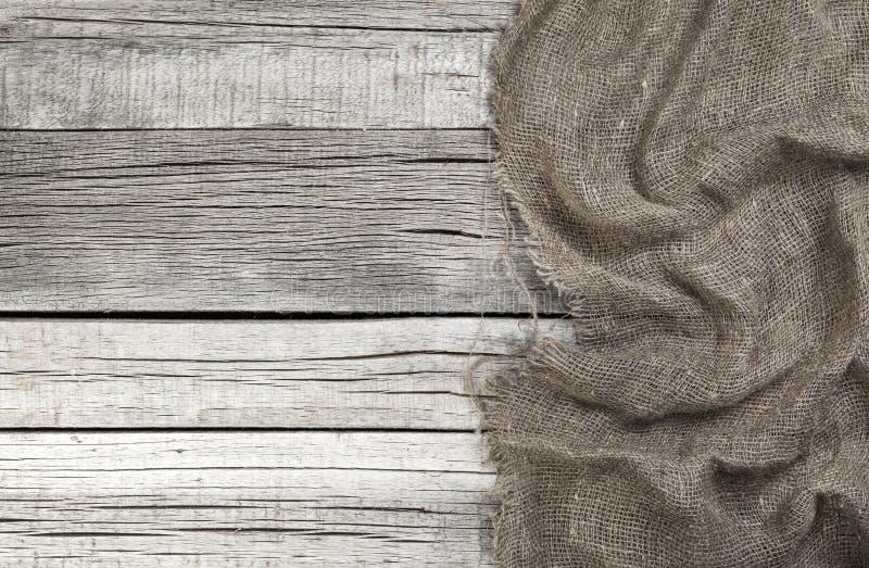 Burlap στο παλαιό γκρίζο ξύλινο υπόβαθρο στοκ φωτογραφία