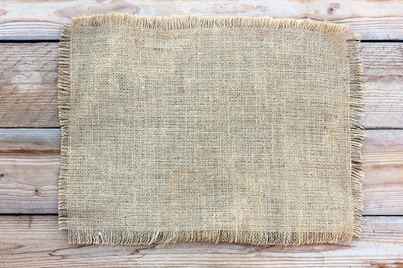 Burlap on the background of the boards, top view. Copy space. stock image