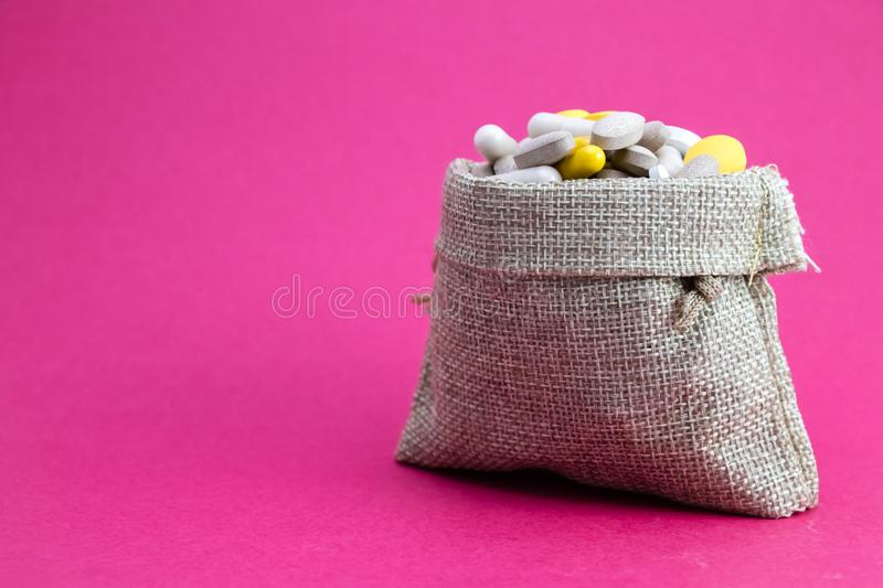 Burlap bag full of drug and medicine pills. Paid medicine. Purchase of medicines pink background. Medicine and pharmacy concept stock photography