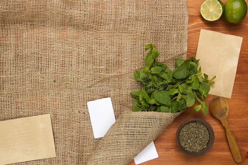 Burlap with a beam of fresh mint. And dry mint in a container royalty free stock photography