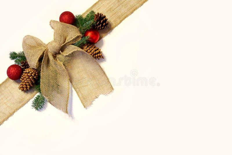 Burlap bożych narodzeń łęk i ornamenty z Pinecones, Odizolowywaliśmy na W zdjęcie stock
