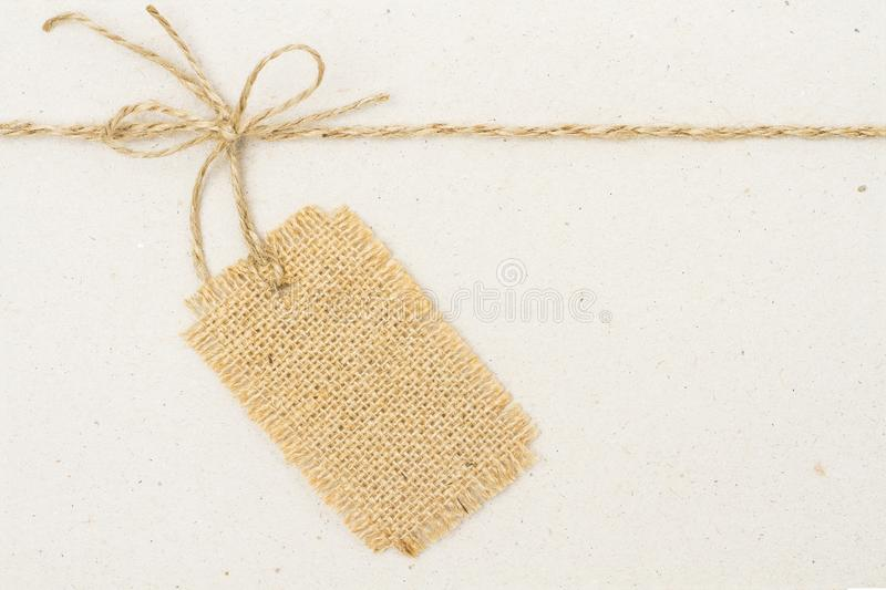 Burlap Cloth Label Tag and Tied Rope Bow over Cardboard Paper royalty free stock photography