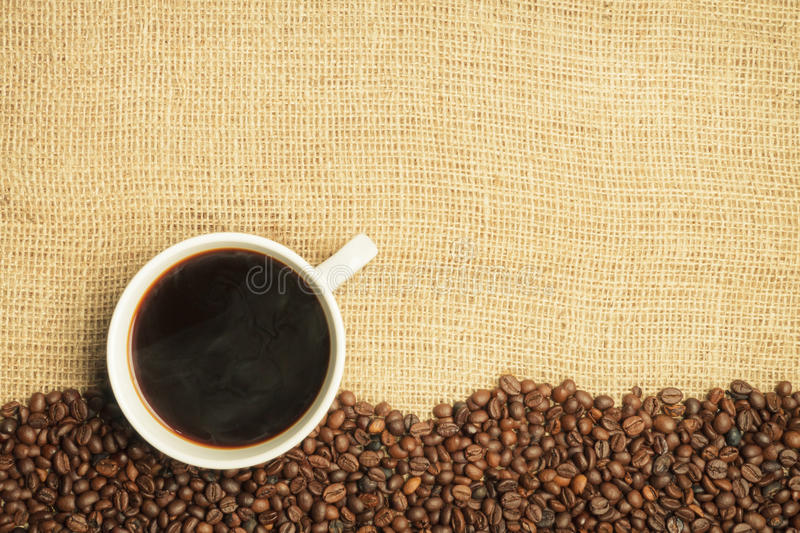 Burlap and coffee beans with cup stock photography