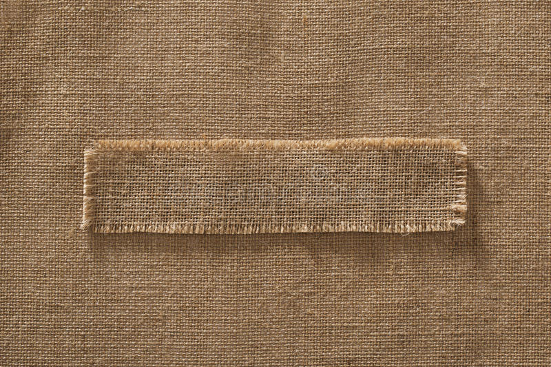 Burlap Fabric Frame Piece Label over Sack Cloth Linen Hessian. Brown Background stock photography