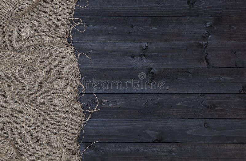 Burlap hessian lub grabić na ciemnym drewnianym tle zdjęcia stock