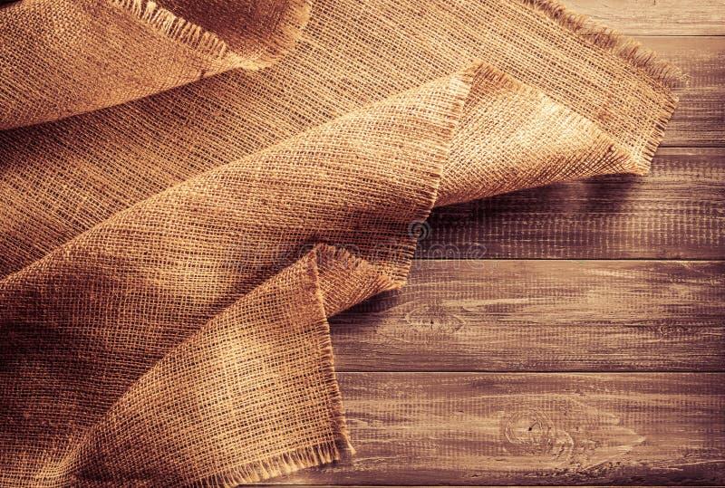 Burlap hessian sacking on wood. En background royalty free stock image