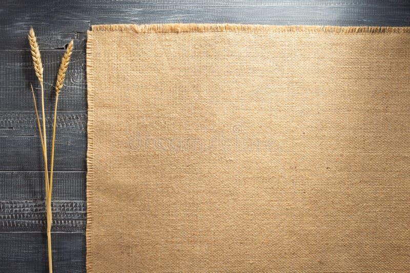 Burlap hessian sacking on wood. En background royalty free stock images