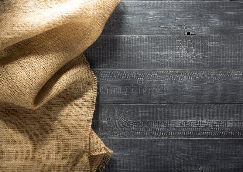 Burlap hessian sacking on wood. En background royalty free stock photos