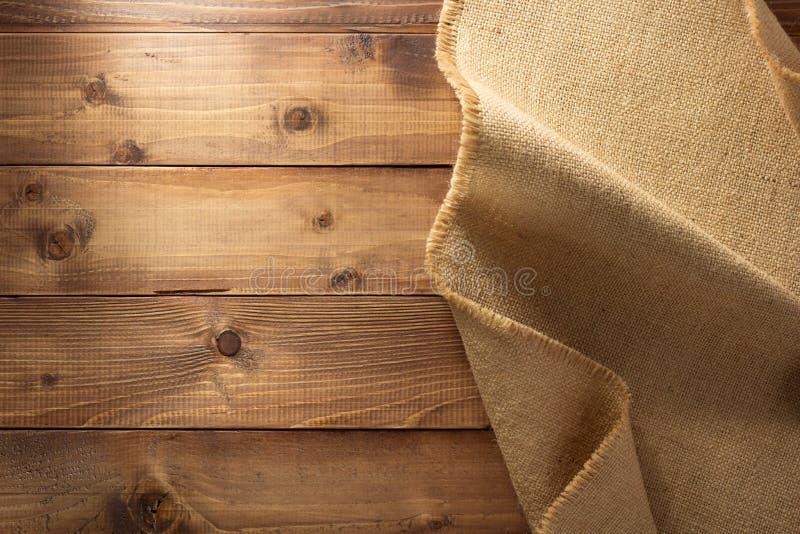 Burlap hessian sacking on wood. En background royalty free stock photo
