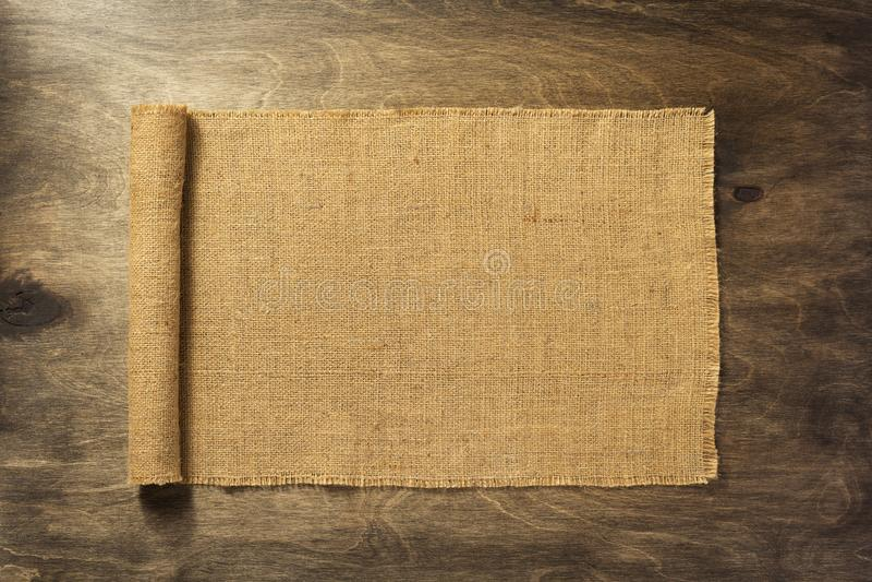 Burlap hessian on wooden background royalty free stock image