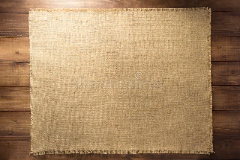 Burlap hessian sacking on wood. En background royalty free stock photography
