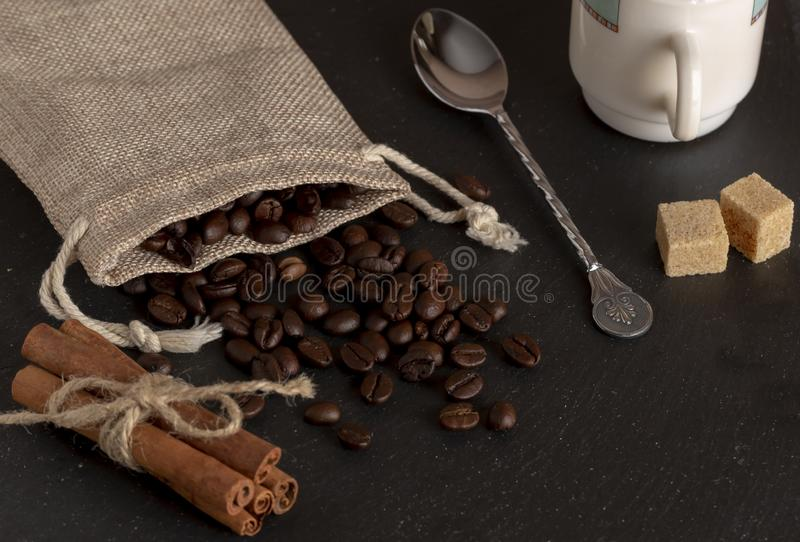 Burlap with roasted coffee beans, cane sugar, coffee cup on stone surface stock photography