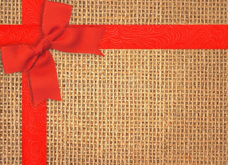 Burlap tekstury tło z czerwonym faborkiem i łękiem obrazy stock