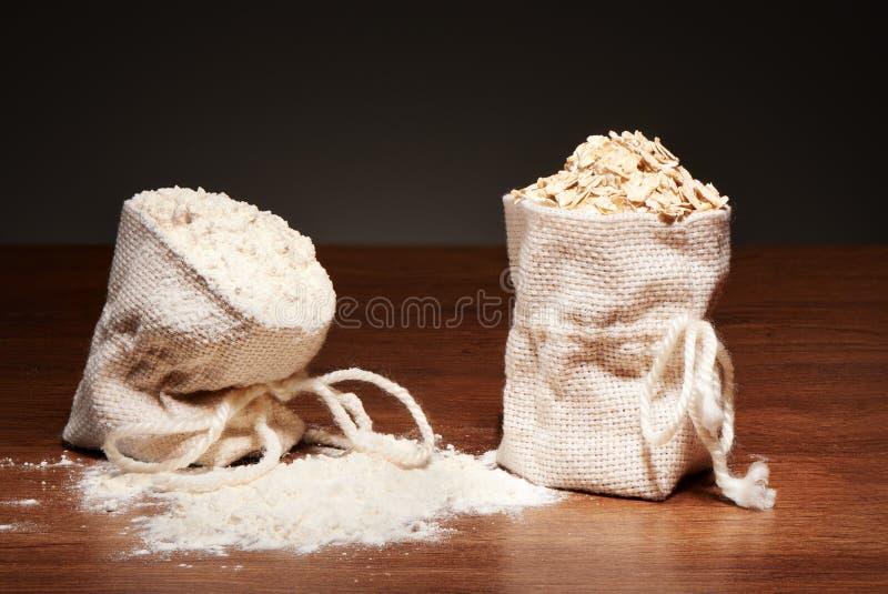 Burlap torby mąki i oatmeal płatki na zmroku stole zdjęcie stock