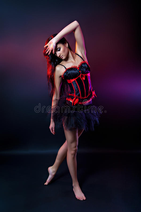 Burlesque brunette dancer in short dress. Lila background, on the stage stock photo