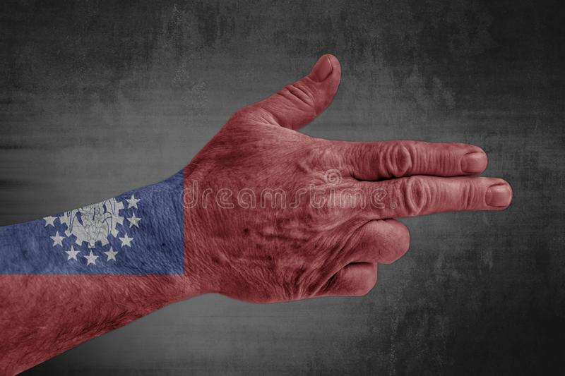 Burma flag painted on male hand like a gun. Isolated on concrete background royalty free stock photography