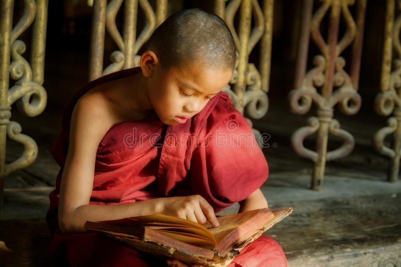 BURMA Little monk or Novice monk are reading the book in the temple of Buddhism Religion in Mandalay Myanmar. stock image