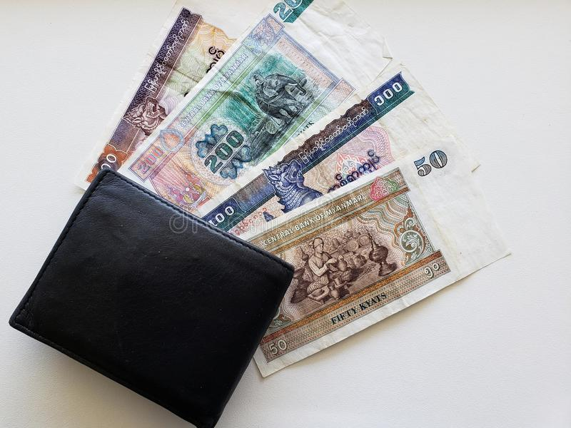 Burmese banknotes of different denominations and black leather wallet royalty free stock image