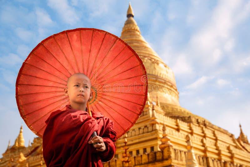 Burmese Buddhist monk walk with umbella in Shwezigon Paya golden pagoda. Temple, bagan, myanmar stock photos