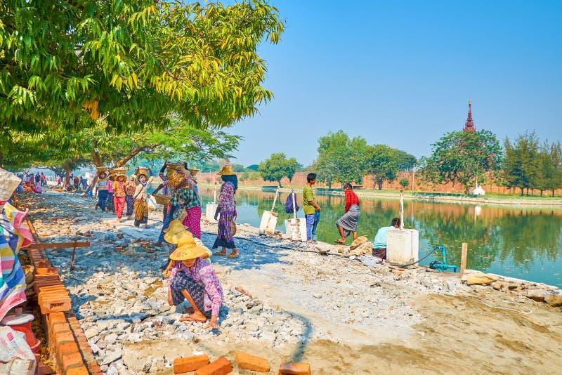 The burmese builders at work in Mandalay, Myanmar. MANDALAY, MYANMAR - FEBRUARY 23, 2018: The road repairing process with manual stone carrying and paving the stock photos