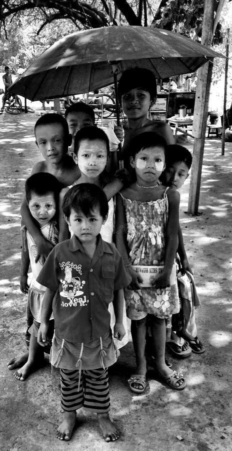 Burmese Children posing with an umbrella. In Mandalay, Myanmar stock photo