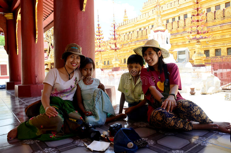 Burmese children take photo with foreigner at Shwezigon Pagoda. Shwezigon Pagoda or Shwezigon Paya is a Buddhist temple located in Nyaung-U, a town near Bagan stock photo