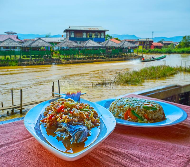 Burmese cuisine, Inle Lake, Myanmar. The tasty dishes of Burmese cuisine in restaurant on Inle Lake - the spicy rice and fish with vegetables are the most stock image