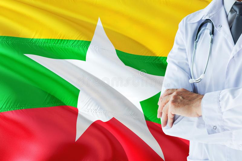 Burmese Doctor standing with stethoscope on Myanmar flag background. National healthcare system concept, medical theme.  stock photography