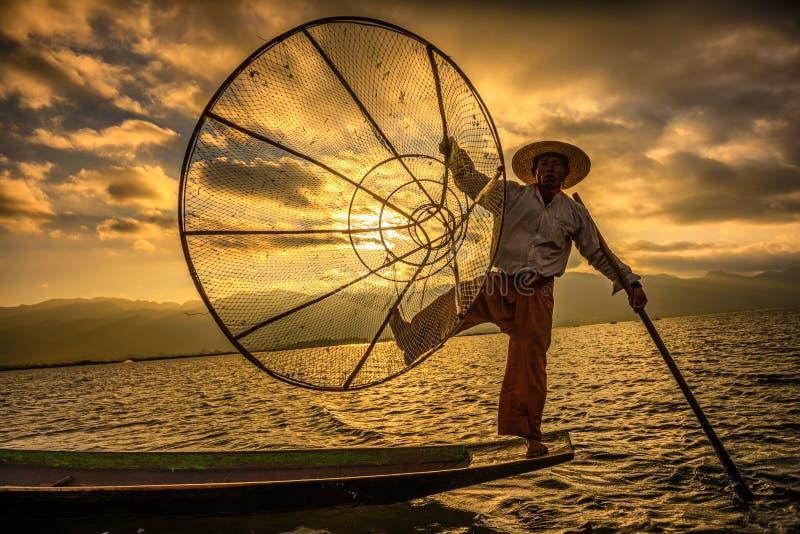 Burmese fisherman on a bamboo boat at sunrise. INLE LAKE, MYANMAR - JANUARY 28, 2016 : Burmese fisherman fishing on a traditional bamboo boat with a handmade net royalty free stock image